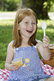 Girl with Applesauce. Small pre-school girl eating a container of applesauce while picnicing in the park stock photos