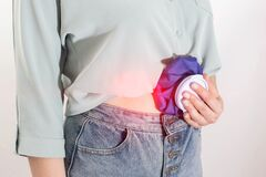 The girl applies cold in a medical bag to relieve abdominal pain and pain relief. The concept of cold compresses for