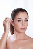 Girl applies fake lashes with tweezers Royalty Free Stock Photos