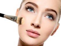 Girl applies tonal foundation on face use makeup brush stock photos