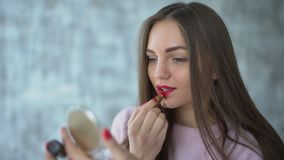 Girl apply lip stick looking in mirror holding hand. 20s model is making perfect look by professional cosmetics close up. Beautiful Woman applying red lipstick stock footage