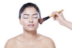 Girl apply makeup by brush in studio Stock Photo