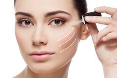 Girl applying anti wrinkle serum Stock Image