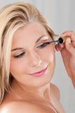 Girl applying black mascara Stock Photo
