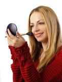 Girl applying blush. Pretty woman applying blush on her cheeks Stock Photography