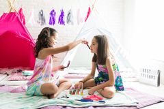 Girl Applying Blush On Best Friend`s Face During Slumber Party. At home stock photo