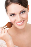 Girl applying cosmetics to her face Royalty Free Stock Photos
