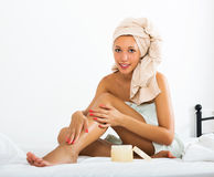 Girl applying cream on legs Stock Image