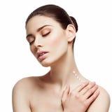Girl applying cream on neck Stock Image
