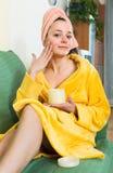 Girl applying cream on skin Stock Photos