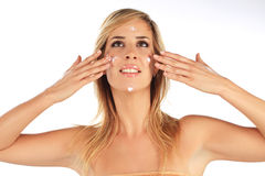 Girl applying creme on her face Stock Image