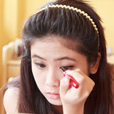 Girl applying eyeliner Royalty Free Stock Photos
