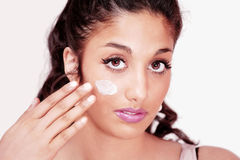Girl applying face cream Stock Image