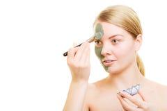 Girl applying facial clay mask to her face Royalty Free Stock Photos