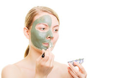 Girl applying facial clay mask to her face Royalty Free Stock Image