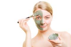 Girl applying facial clay mask to her face Stock Photos