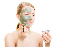 Girl applying facial clay mask to her face Royalty Free Stock Photography
