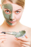 Girl applying facial clay mask to her face Stock Photo