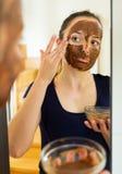 Girl applying a facial mask Stock Images