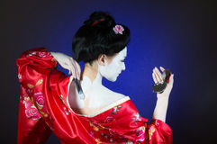 Girl applying geisha makeup. Studio portrait of a girl applying geisha makeup, back view stock photo