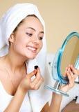 Girl Applying Lip Gloss Royalty Free Stock Images