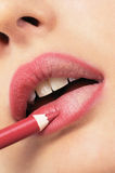 Girl applying lip liner. Picture of young girl applying lip liner with a pencil Stock Photo