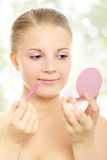 Girl applying lip pencil-makeup. Young woman applying lip pencil-makeup Royalty Free Stock Image
