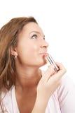 Girl applying lipstick over white Stock Photography