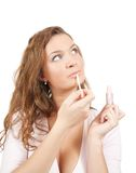 Girl applying lipstick over white Royalty Free Stock Photos