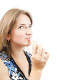 Girl applying lipstick over white Stock Image