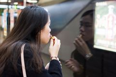 Girl applying lipstick while waiting for the metro Royalty Free Stock Photo