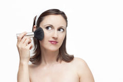 Girl applying make up. Caucasian young woman applying powder on the cheeks on white background Stock Images