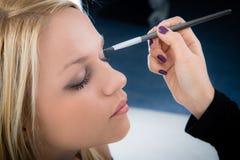 Girl applying make-up. By make-up artist Stock Photos