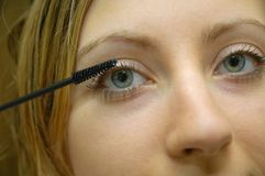 Girl applying make up. In front of mirror Royalty Free Stock Photo