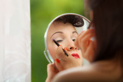 Girl applying make up with brush Royalty Free Stock Images
