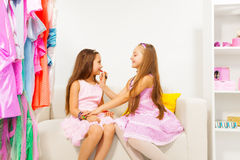Girl applying make-up on her friend while sitting Royalty Free Stock Photo