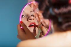 Girl applying make up red lipstick Stock Images