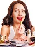Girl applying makeup. Stock Image