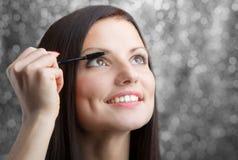 Girl applying mascara stock photos