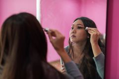 Girl applying mascara to eyelashes. Young Asian woman doing make up of eyelashes in front of mirror in pink room. Cute girl applying mascara for new day concept Stock Photos