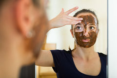 Girl applying mask for facial skin care. Adult girl applying mask for facial skin care Stock Images