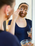 Girl applying mask for facial skin care. Young girl applying mask for facial skin care Stock Photos