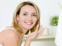 Girl applying moisturizer  cream on face Stock Image