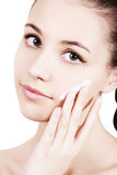 Girl applying moisturizer cream on face. Royalty Free Stock Photos
