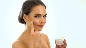 Girl applying moisturizer on your face. Slow motion. stock video