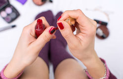 Girl applying nail polish in bed Stock Photography