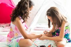 Girl Applying Nail Polish On Friend`s Fingers During Sleepover. At home royalty free stock photography