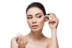Girl applying serum. Beautiful young woman applying anti-ageing moisturizing serum to under eye area. Isolated over white background. Copy space royalty free stock photos