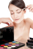 Girl applying shadow by brush on the eyelid. Royalty Free Stock Image