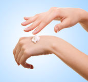 Girl applying some white lotion on her hand Stock Images